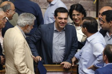 Greek Prime Minister Alexis Tsipras (C) is congratulated by lawmakers after a voting session at the Parliament in Athens, Greece, July 11, 2015. The Greek parliament voted overwhelmingly on Saturday in favour of authorizing the left-wing government of Tsipras to negotiate with international creditors on the basis of a reform programme unveiled this week.REUTERS/Christian Hartmann  - RTX1JYAB